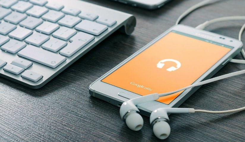 Imagen de un celular con unos audifonos conectados