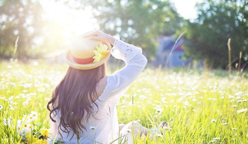Imagen de una mujer de espaldas con un sombrero en dia soleado