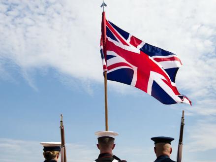 Imagen de una mujer y dos hombres izando la bandera de Inglaterra