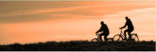 Imagen de dos personas montando bicicleta en el atardecer