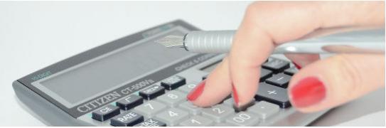 Imagen de la mano de una mujer tecleando una calculadora