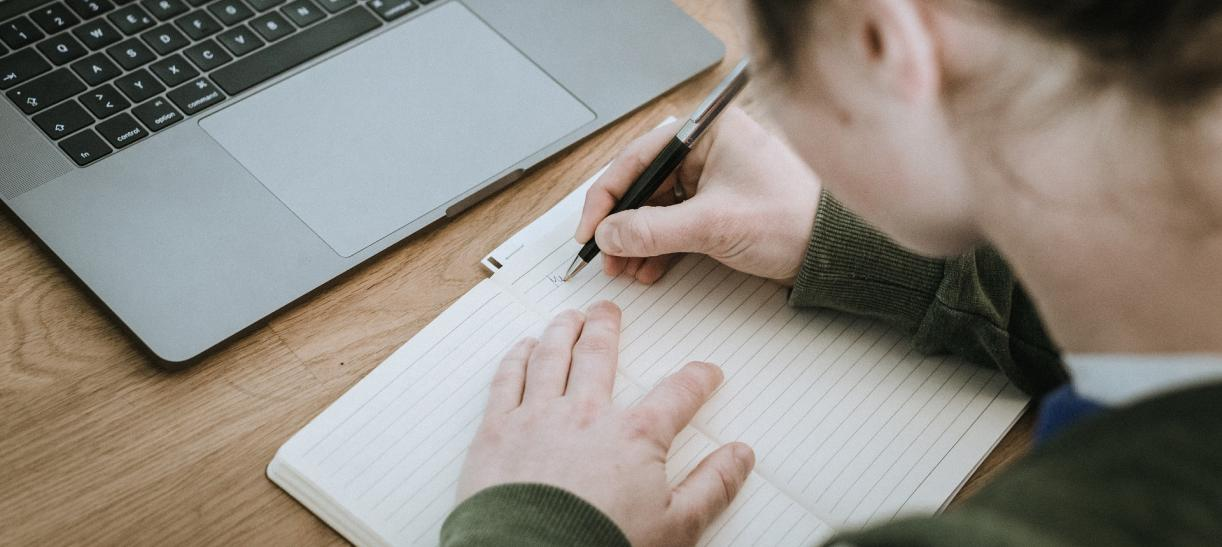 Mujer escribiendo frente a computador