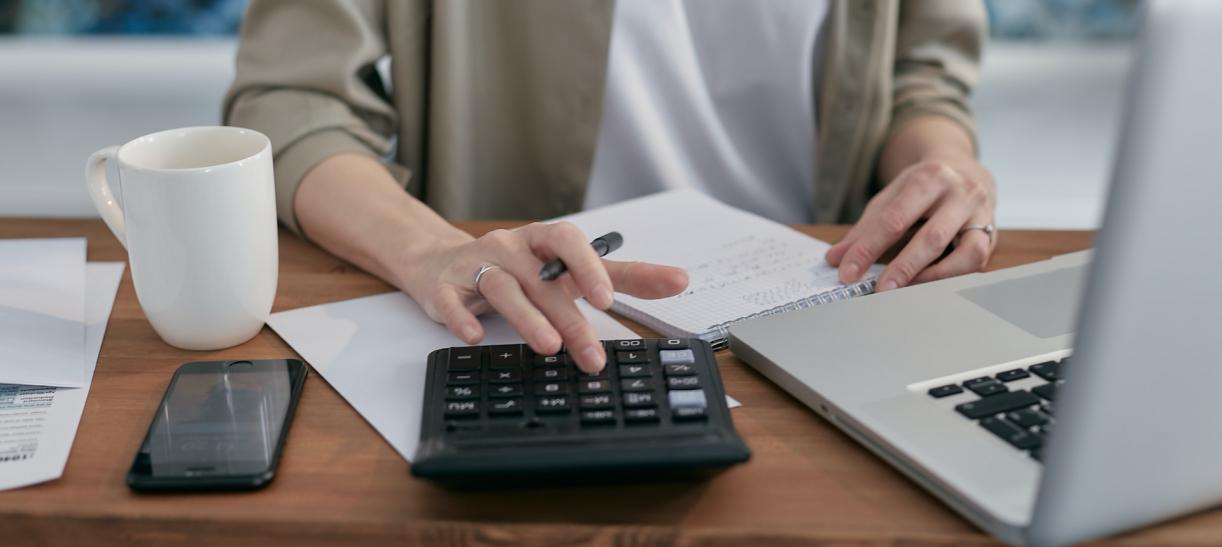mujer usando calculadora finanzas como evitar deudas