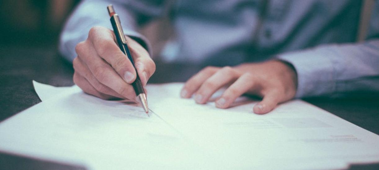 Imagen de un hombre firmando un documento
