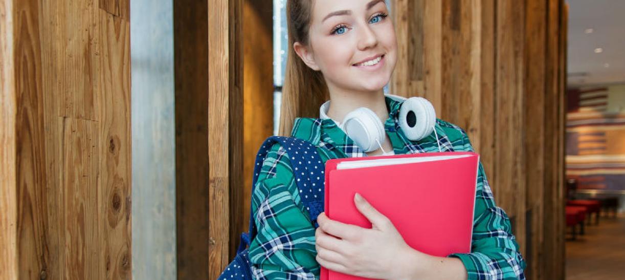 Imagen de una mujer rubia de ojos azules con un libro rojo entre sus brazos