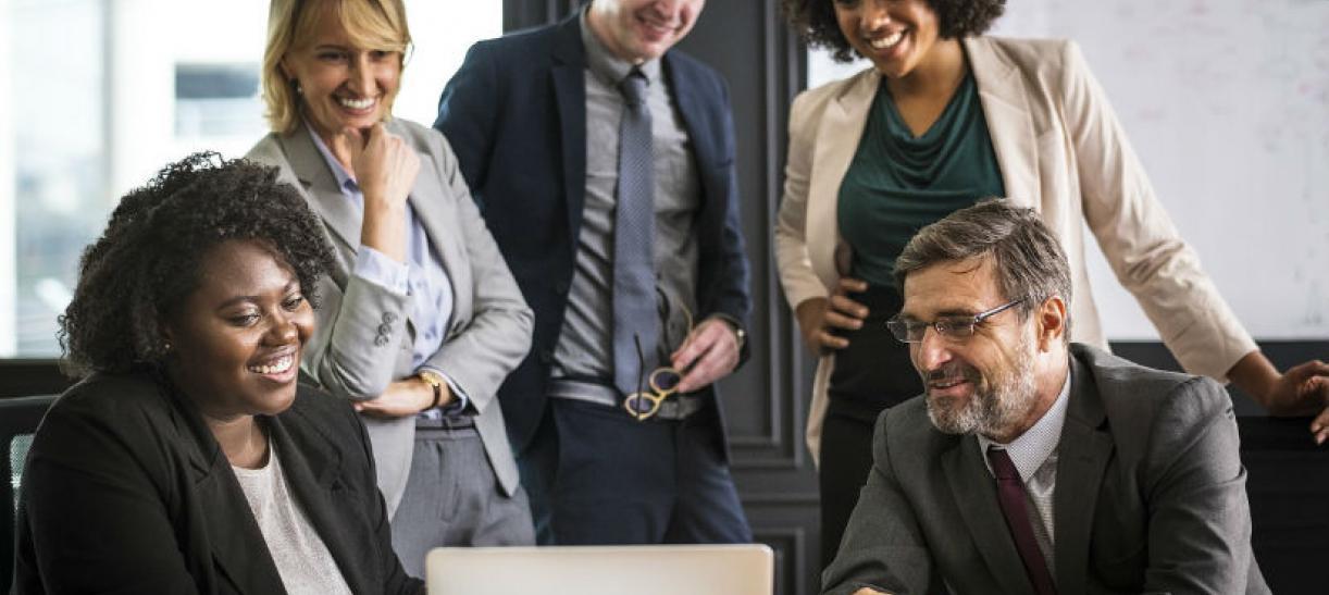 Imagen de varias personas conversando y mirando a un computador