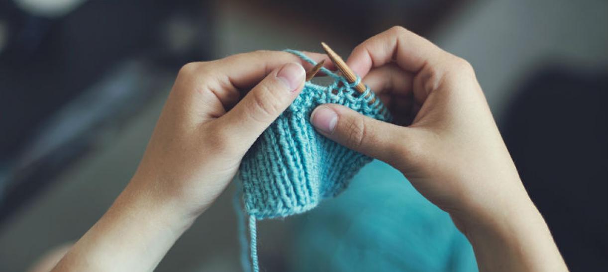 Imagen de unas manos de mujer tejiendo