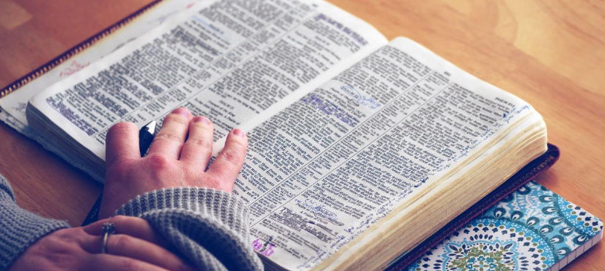 Imagen de las unas manos encima de un libro abierto