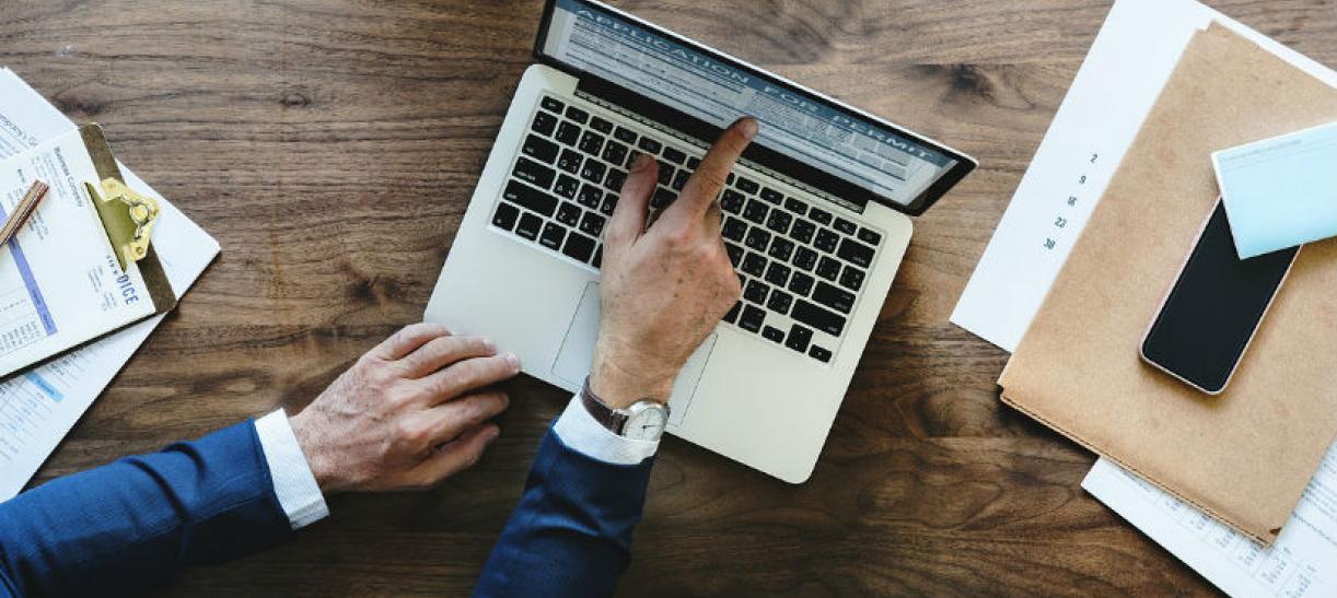 Imagen de un hombre señalando la pantalla del computador