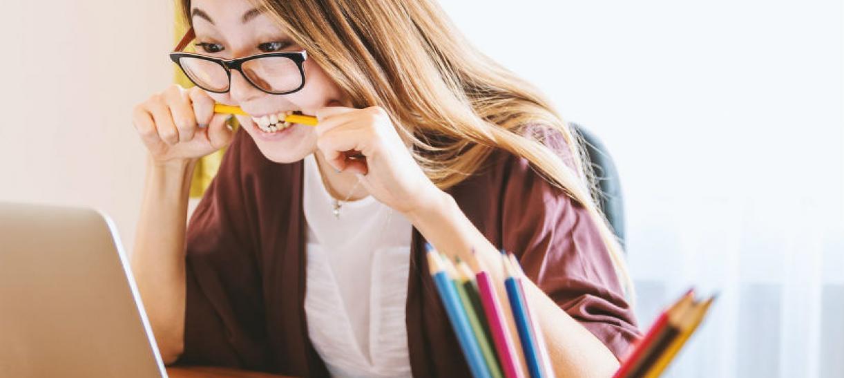 Imagen de una mujer mirando la pantalla del computador con un lápiz en la boca