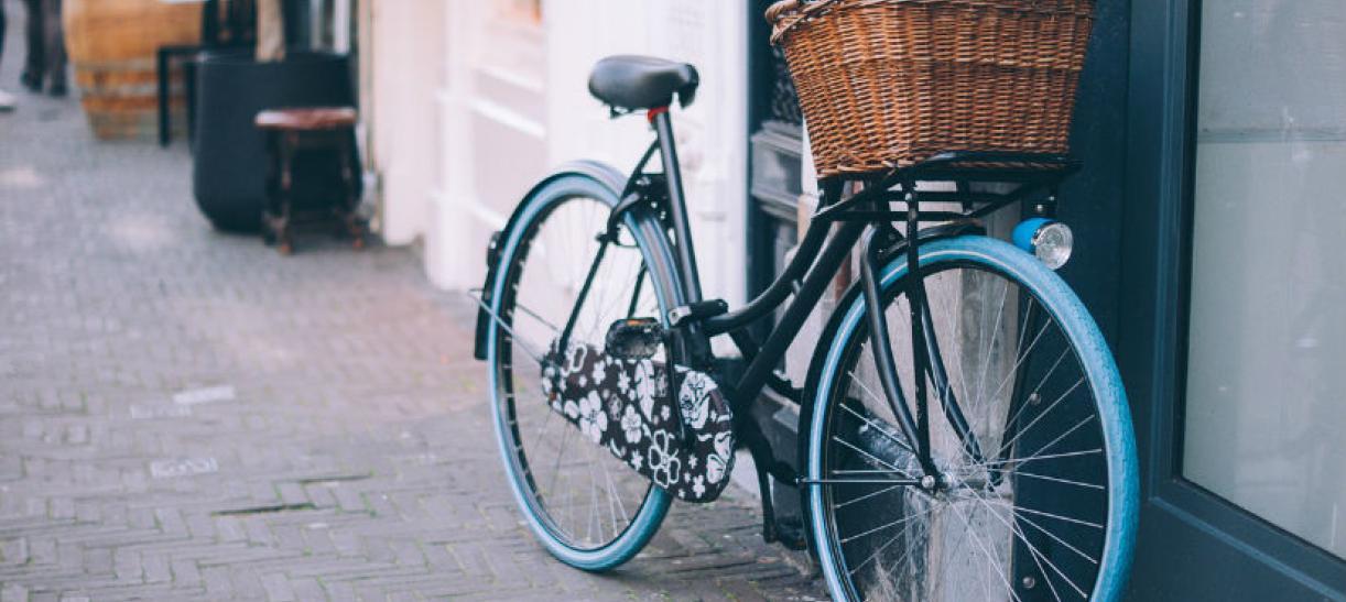 Imagen de una bicicleta con canasta recostada frente a una pared