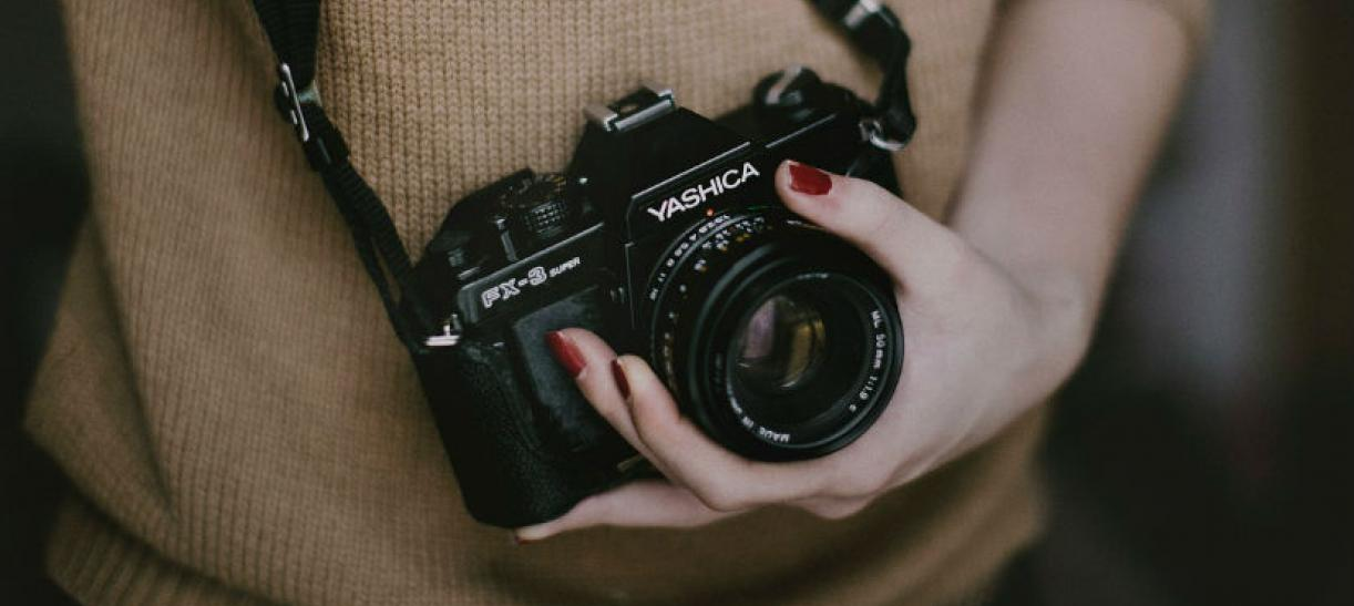 Imagen de una mano de mujer sosteniendo una cámara fotográfica