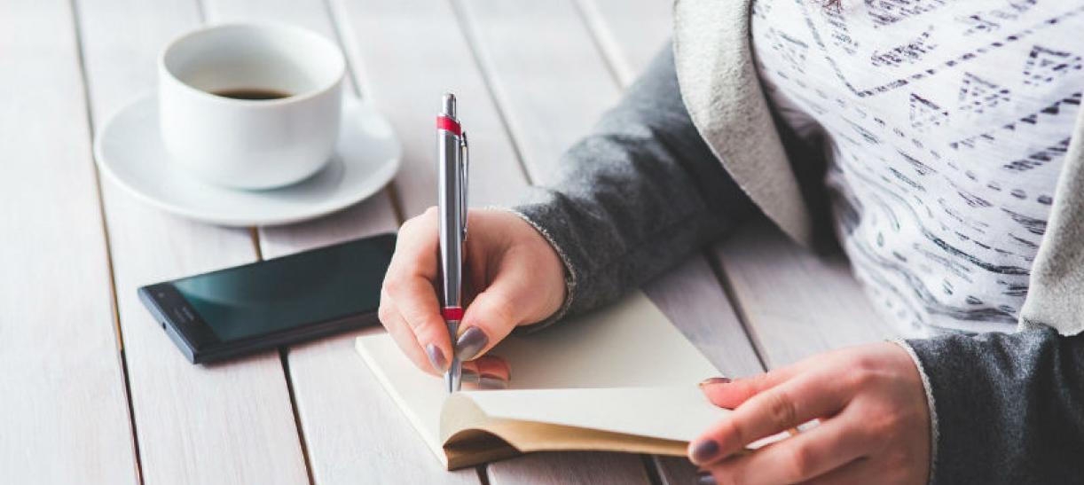 Imagen de una mujer tomando notas con un celular y un pocillo de café