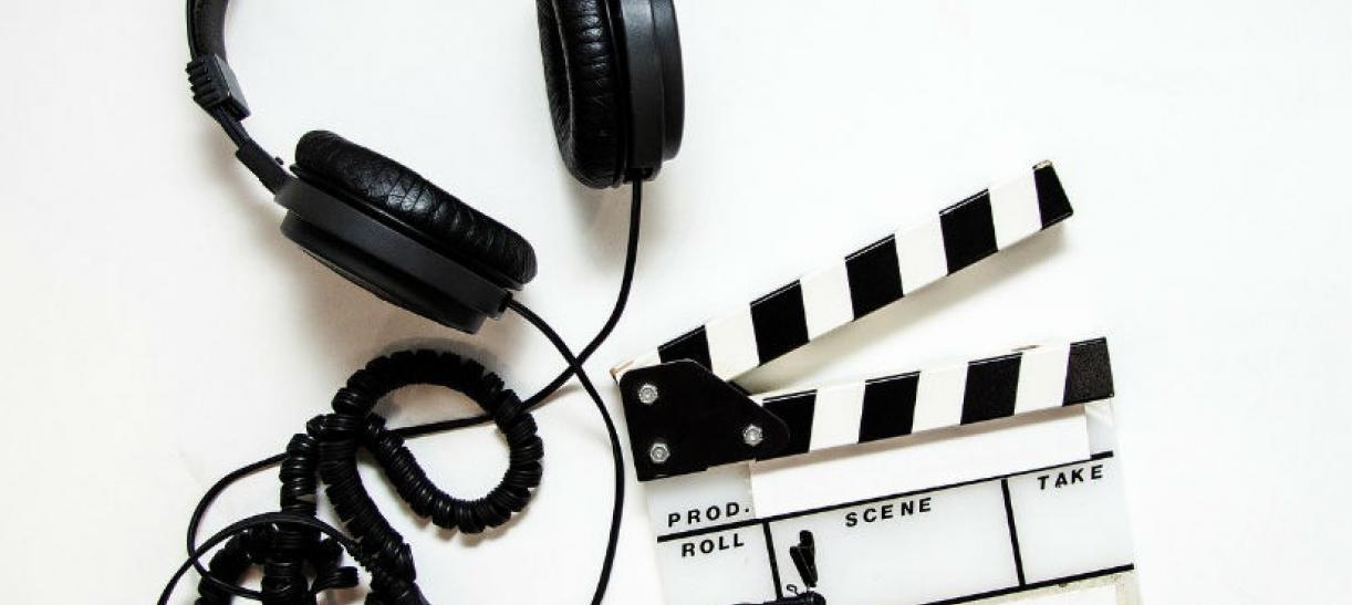 Imagen de unos audifonos y una claqueta de cine