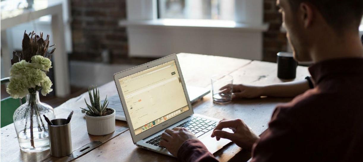 Imagen de unas manos encima de un computador portatil