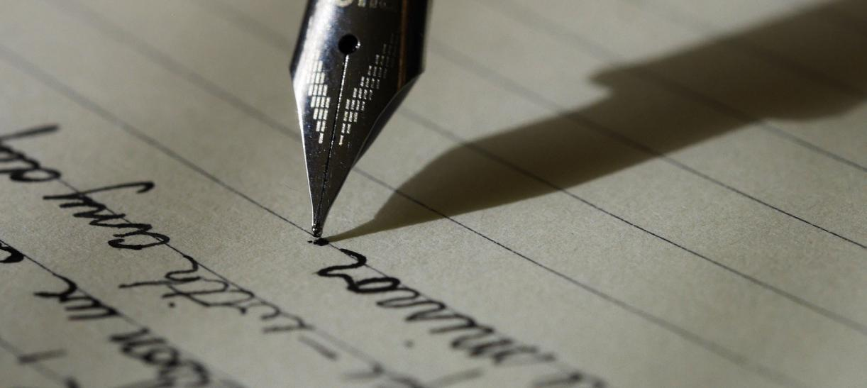 Imagen de una pluma escribiendo en papel