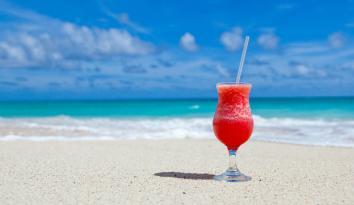 Imagen de un coctel en medio de la playa