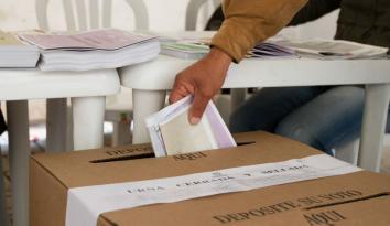 Imagen de una mano depositando un voto en una urna de cartón