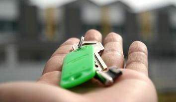 Imagen de una mano abierta con las llaves de una casa en un llavero verde