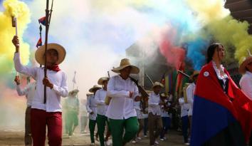 Imagen de varias personas festejando con bengalas de color amarillo, azul y rojo