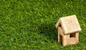 Imagen de una casita pequeña de madera sobre un marco de cesped