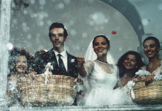 Una pareja joven celebra su matrimonio desde un balcón