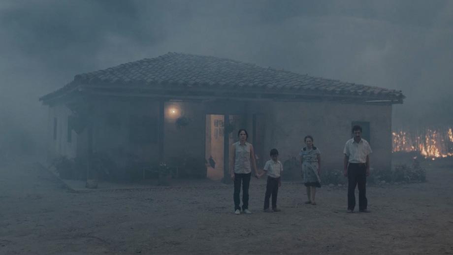 Una familia campesina espera afuera de una casa que se incendia