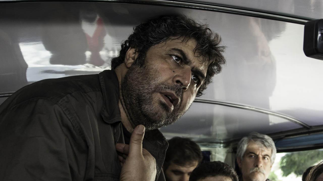 Hombre iraní haciendo a un reclamo a cámara junto a otras personas de su misma nacionalidad