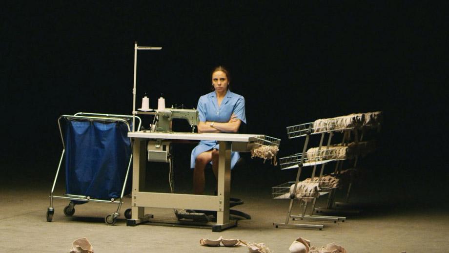 Una mujer cruzada de brazos está sentada frente a una máquina de coser