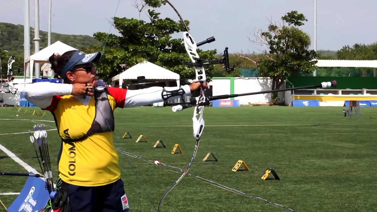 Sara López, deportista de tiro con arco se prepara para hacer un disparo al blanco
