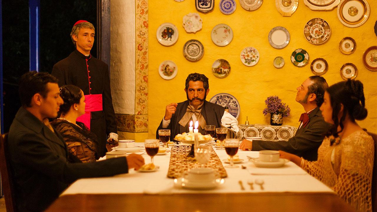 Hombres y mujeres en casa colonial sentados en la mesa