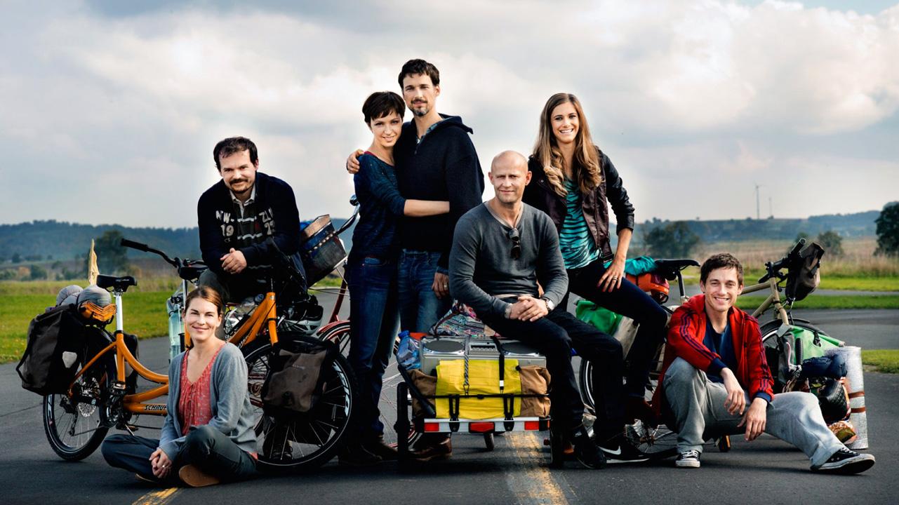 Un grupo de jóvenes sonríen en la mitad de una carretera europea.