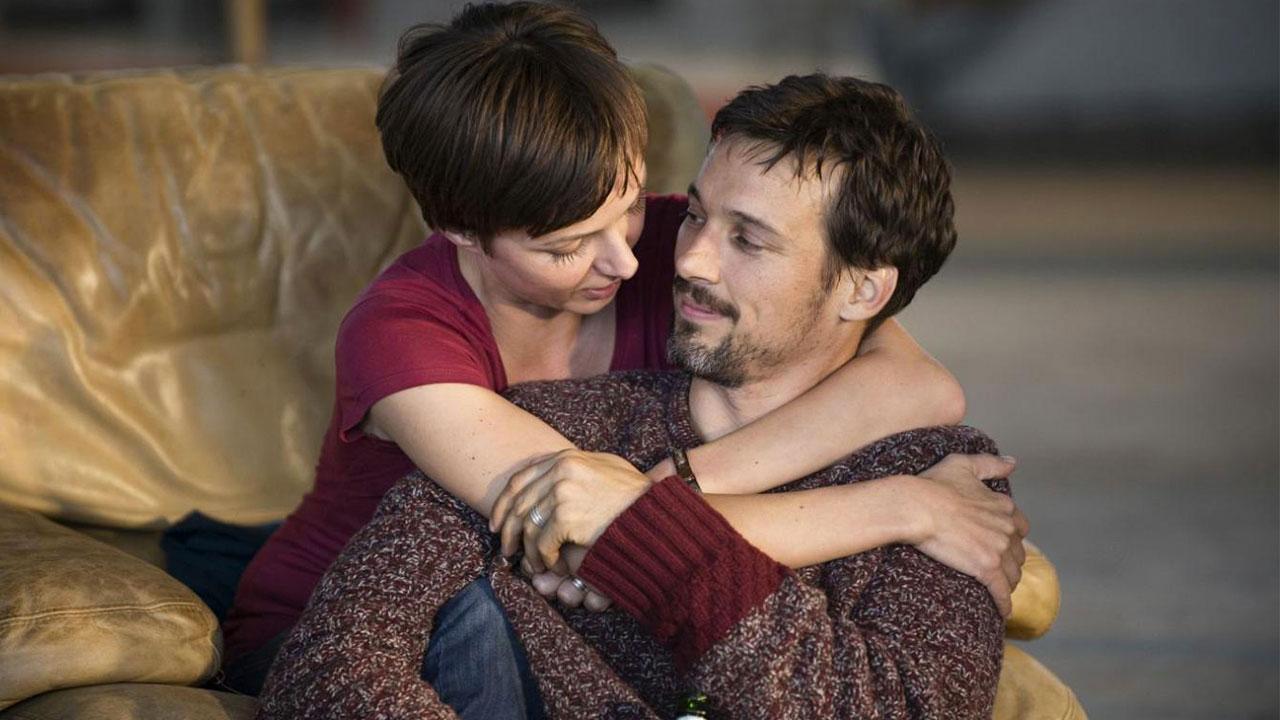 """Una pareja joven se abraza y sonríe. Florian David Fitz y Julia Koschitz, protagonistas de la película alemana """"Camino a la fortaleza""""."""