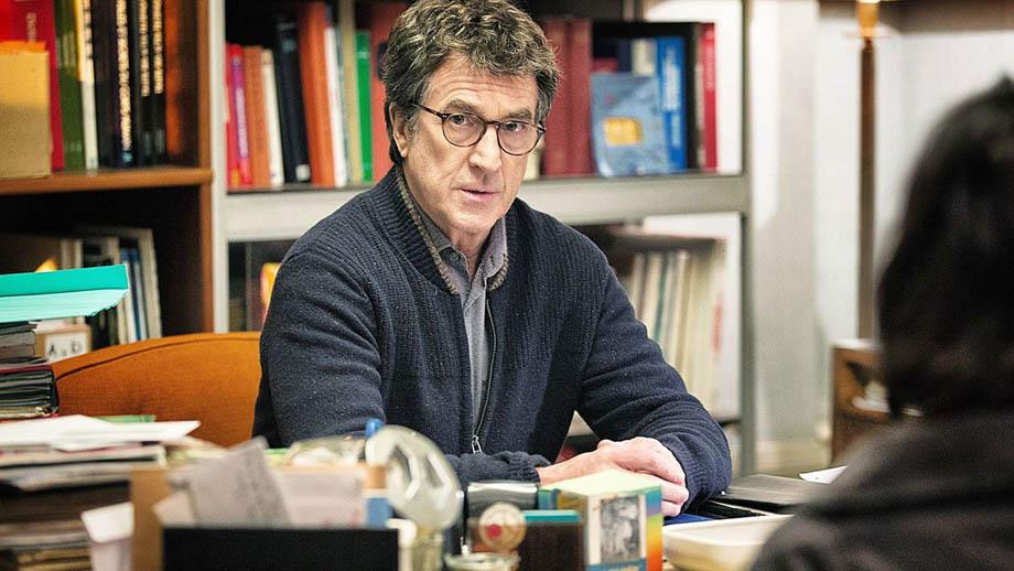 Un hombre de mediana edad está sentado en su escritorio