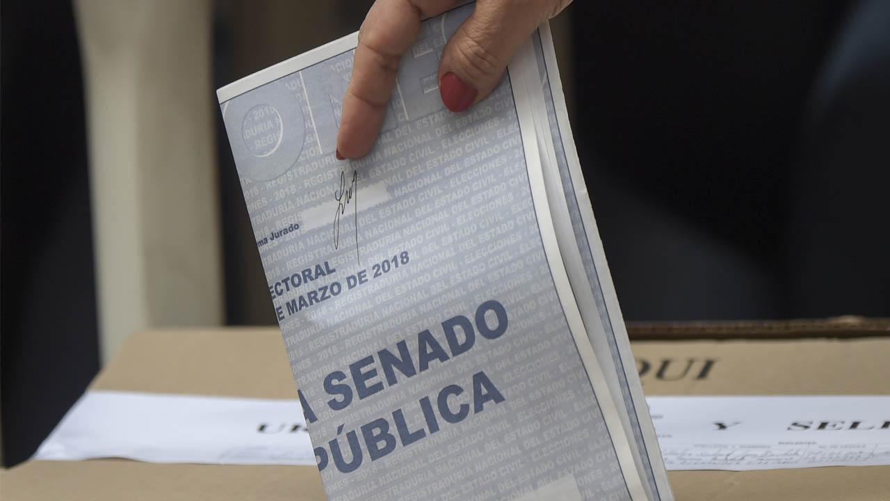 Una mano se acerca con su tarjetón hacia la urna electoral