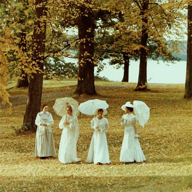 Cuatro mujeres de blanco caminan en un jardín - Imagen de la película Gritos y susurros de Ingmar Bergman