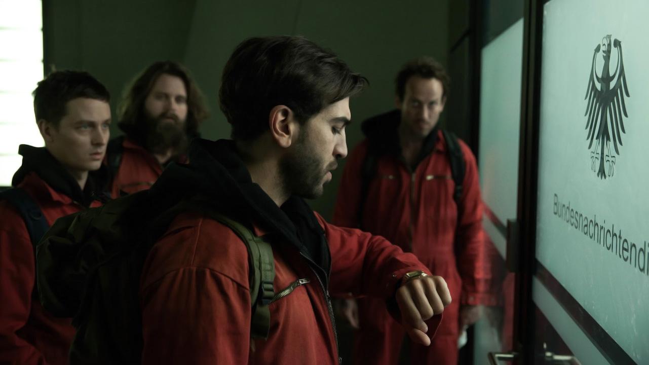 Un grupo de hackers en uniforme rojo ingresan a un edificio del gobierno en la película Hackers: ningún lugar es seguro.
