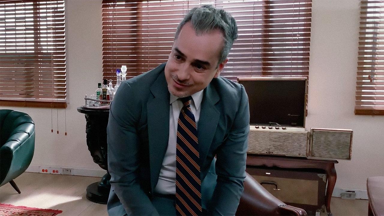 Un político de saco y corbata sonríe en su despacho.