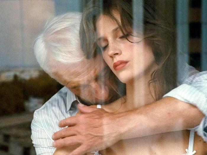 Un hombre mayos abraza y besa a una joven en una ventana