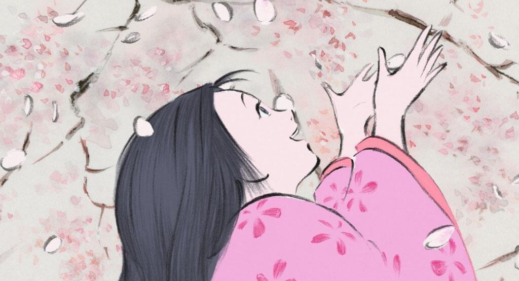 Un joven sonríe rodeada por capullos de cerezo en flor.