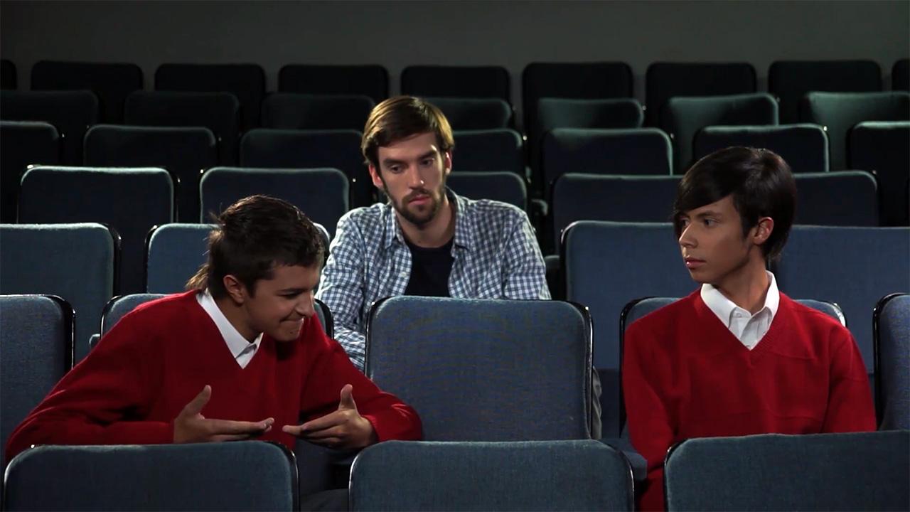 Dos estudiantes de colegio conversan en las sillas de un auditorio, un joven los observa