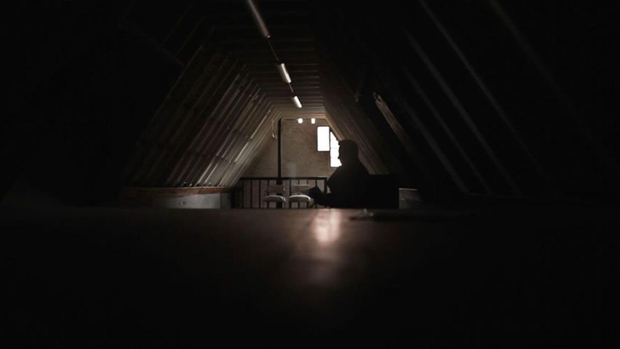 Fotograma del documental 'La venganza de Jairo', donde el cineasta aparece al final de un altillo en oscuridad.