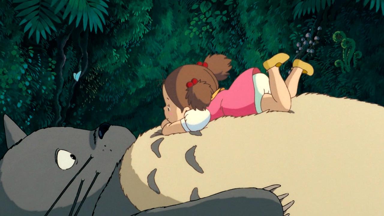 Una niña descansa sobre la barriga de un gigante felpudo llamado Totoro