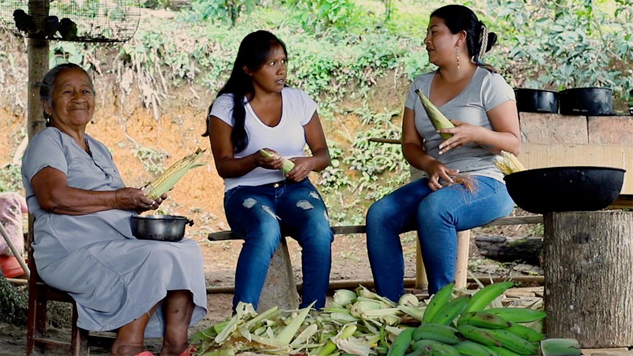 Varias mujeres indígenas de diferentes edades conversan mientras desgranan maíz