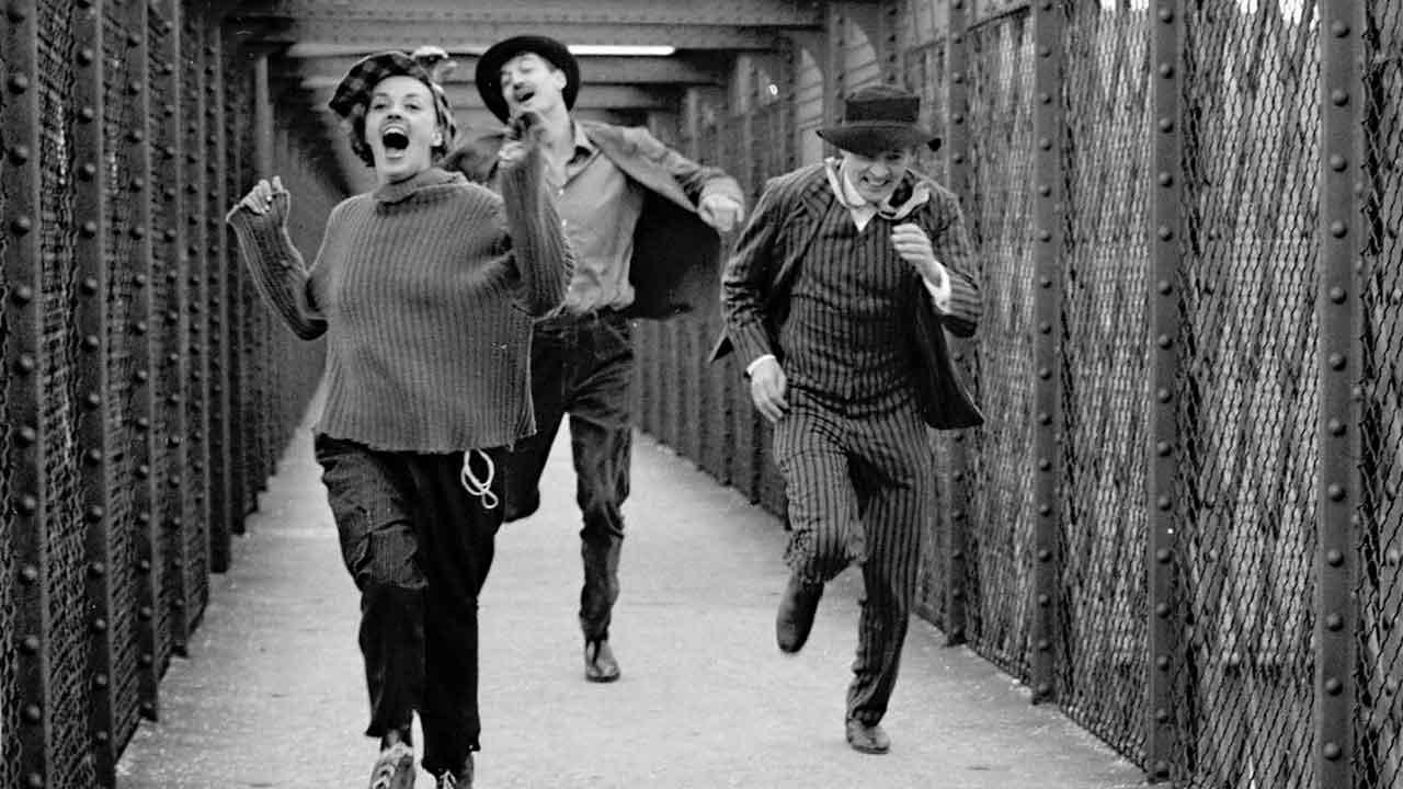 """Tres personas corren por un puente peatonal en la película """"Jules y Jim"""" de Truffaut"""