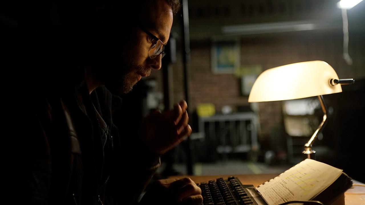 Periodista sentado trabajando en su escritorio