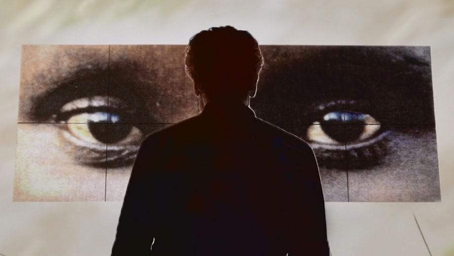 Alfredo Jaar viendo su propia obra en exposición
