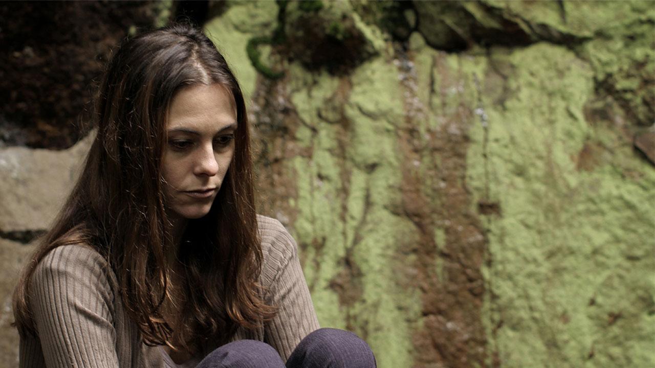 """Mujer afectada sentada y sola en la película """"El resquicio"""""""