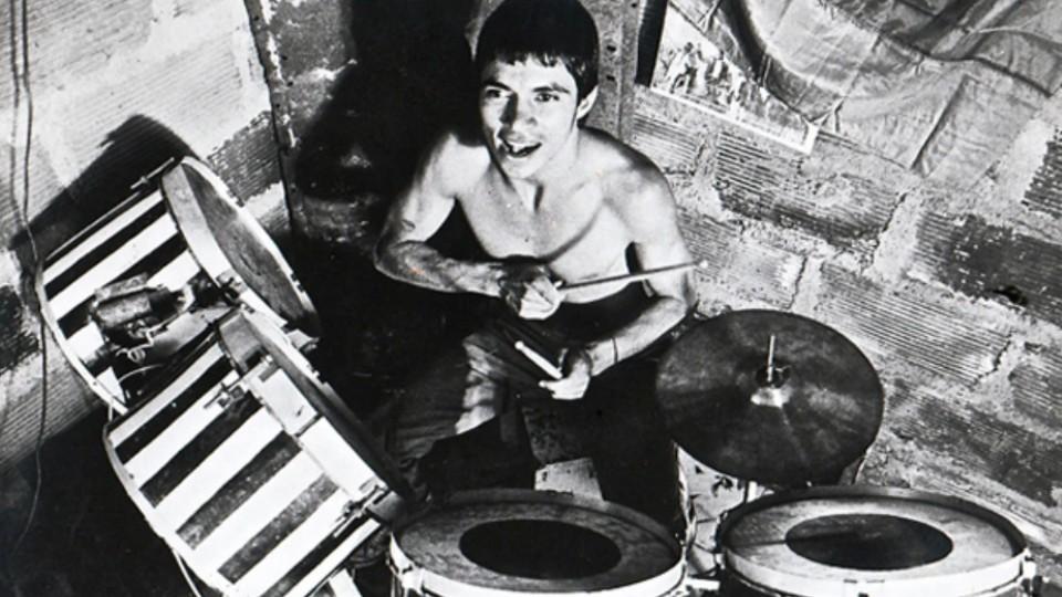 Un joven sonríe mientras toca la batería