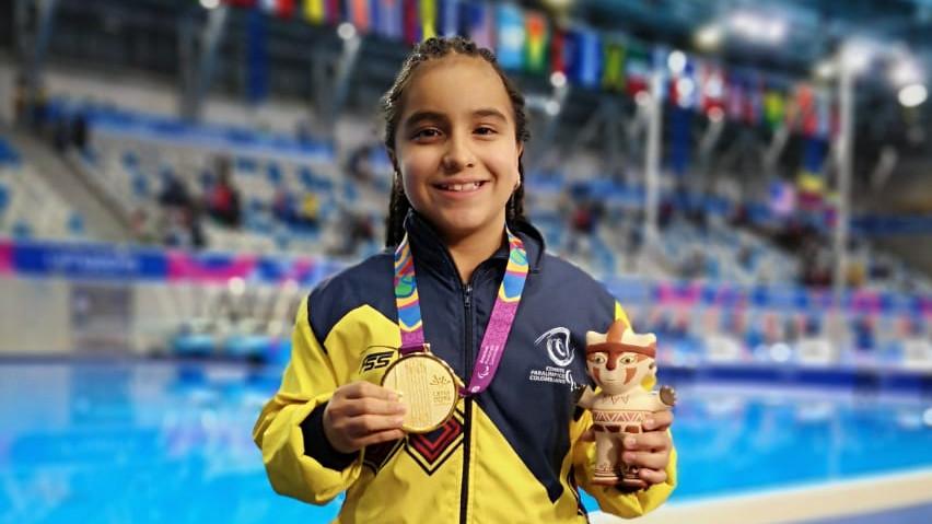 La nadadora colombiana Sara Blanco sonríe con una de las medallas de oro que ganó en los Juegos Parapanamericanos Lima 2019, con el centro acuático de esa cidad de fondo.